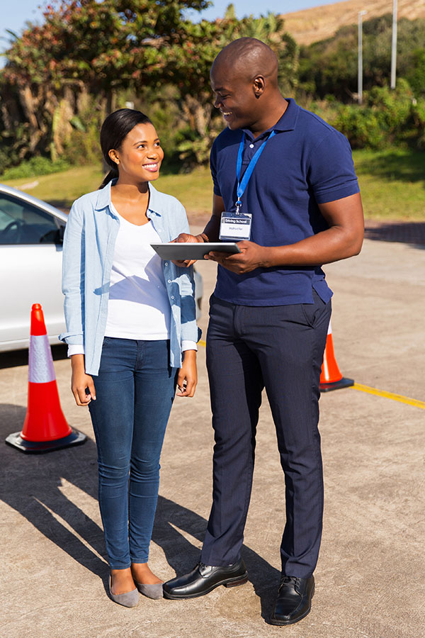 Man with tablet and woman preparing for driver test
